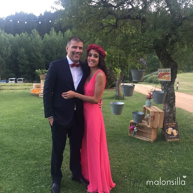 Pareja invitados a boda en un jardín decorado con cajas de madera, ella con vestido rosa largo y corona de flores preservadas buganvilla