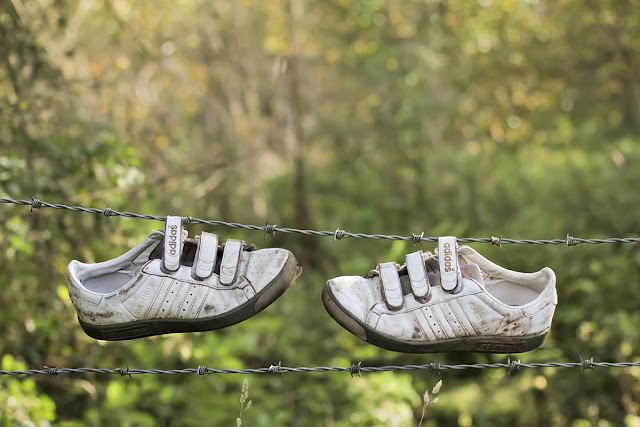 trainers hanging from wire fence