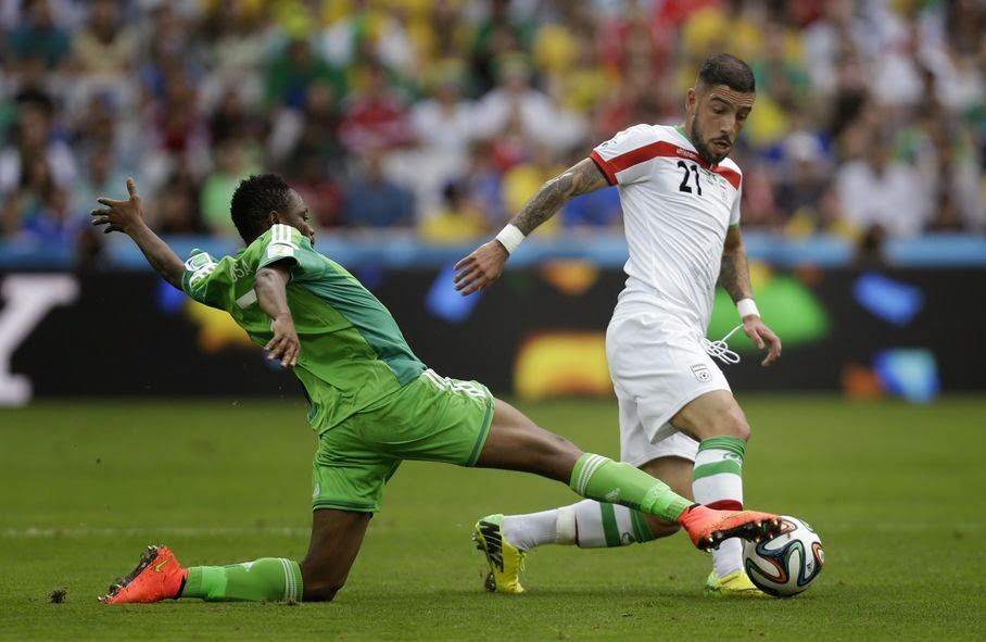 Nigeria's Ahmed Musa, left, challenges Iran's Ashkan Dejagah during the group F World Cup soccer match between Iran and Nigeria at the Arena da Baixada in Curitiba, Brazil, Monday, June 16, 2014.