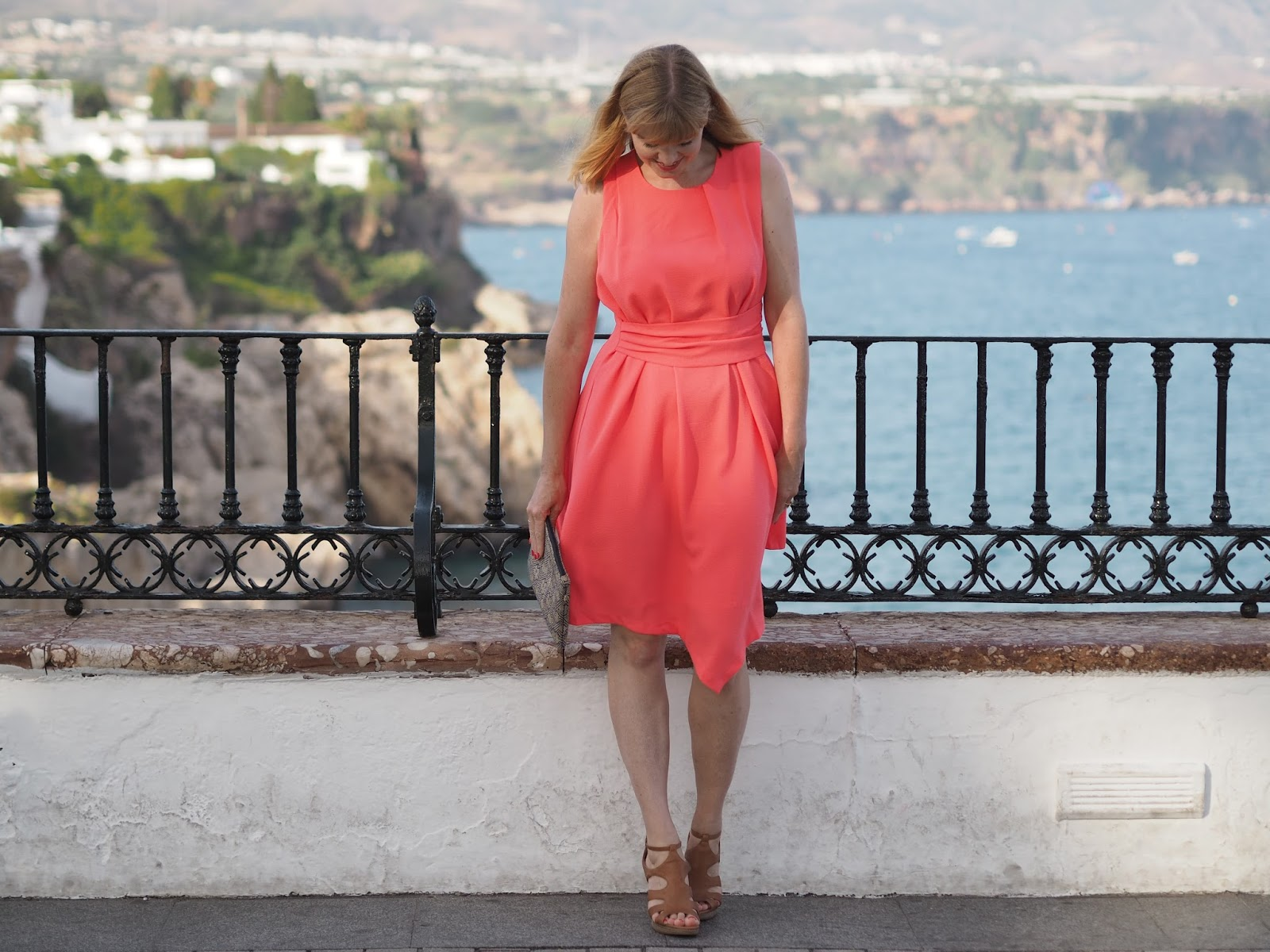 Coral asymmetric dress with sandals and gold star jewelery