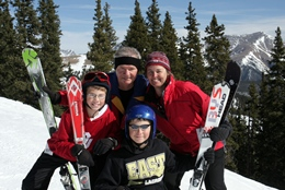 Family of 4 posing with their skis on a sunny day with the ski area in the background.