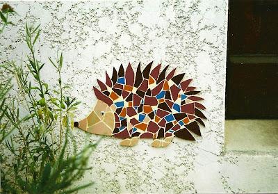 fresque murale Décor de hérisson en tesselles de mosaïque dans un jardin sur un mur de maison en extérieur par mosaiste severine peugniez