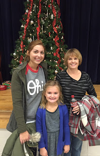Lady with green coat and Ohio State shirt, woman with black and grey stripped shirt, and young girl with blue jacket and grey dress standing in front of a Christmas tree