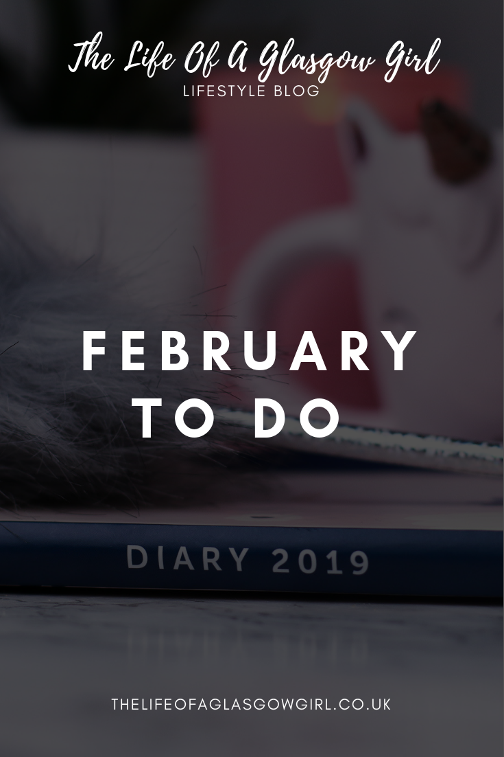 Pinterest image for February To Do List on Thelifeofaglasgowgirl a busyb 2019 diary on a marble counter top with a grey fluffy pen on top of it. There is a white unicorn light in the background and a pink candle.