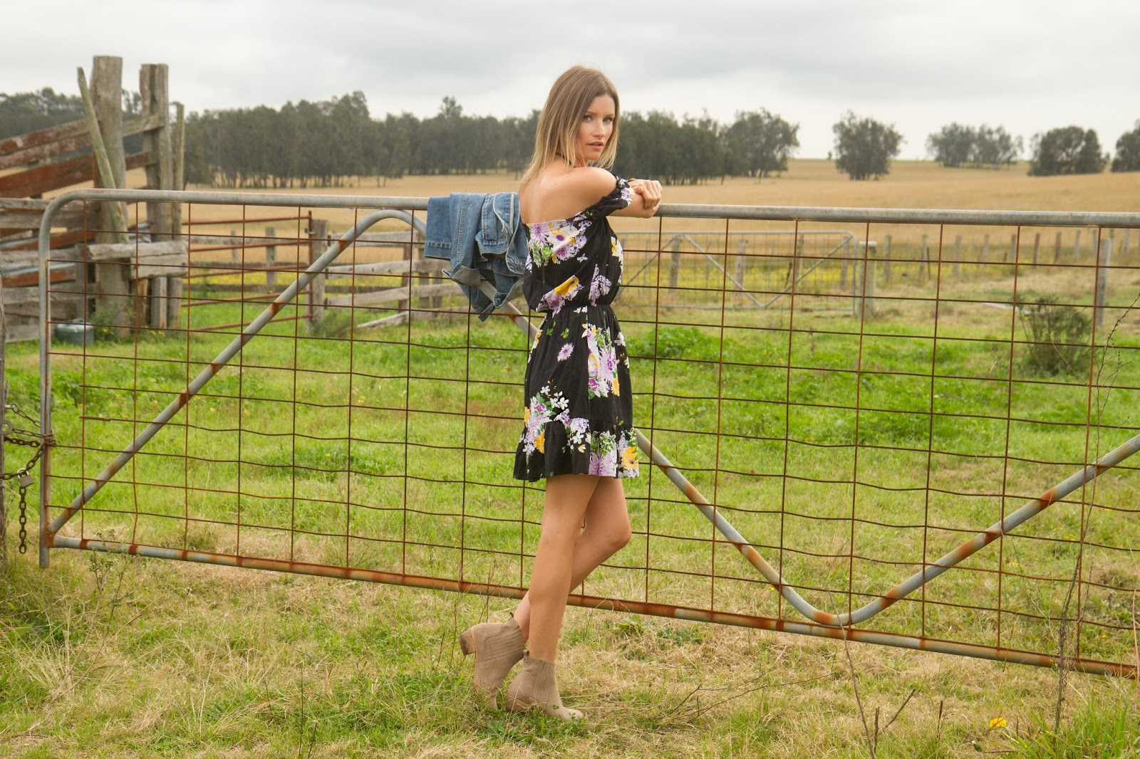 Fashion and travel blogger, Alison Hutchinson, is wearing a KAYVALYA off the shoulder dress in black floral print in Hunter Valley, Australia