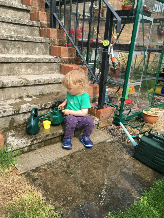 toddler-sat-on-step-playing-with-water