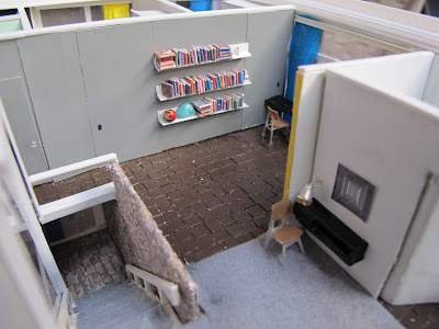 Interior of a 1/48-scale mid-century modern house playroom and study corner, with stone-edged stairs leading downwards.