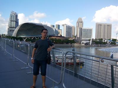 Berfoto dengan latar belakang gedung Esplanade dan Singapore River