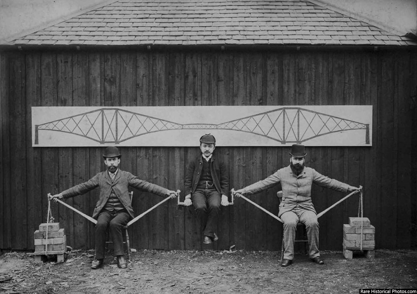 Project engineers demonstrating the cantilever principles of the Forth Bridge in Scotland, 1887.