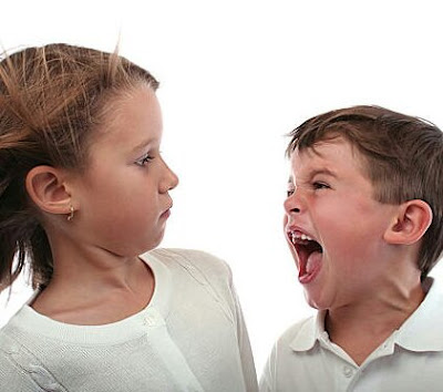A young boy yelling at his sister while she leans back with a look of confusion.