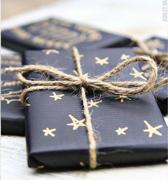 Um papel preto , uma caneta dourada para desenhar as estrelas e cordão de ráfia para o laço