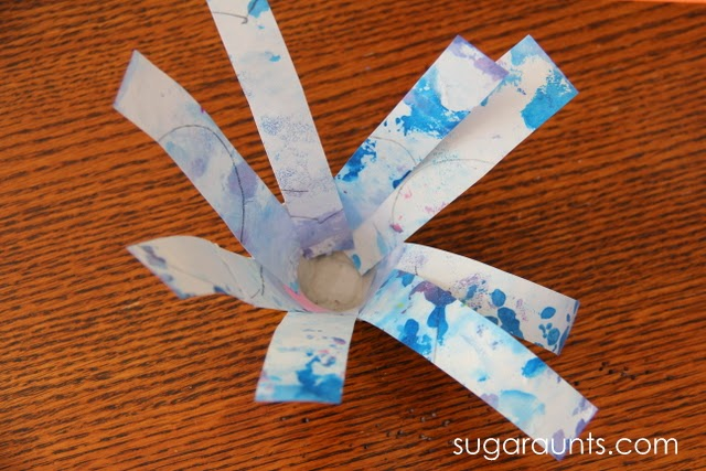 Tape strips of recycled art projects into an egg carton to create a spring flower craft.