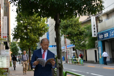 Magazine-reading man on Kojimachi sidewalk, Chiyoda-ku, Tokyo, Japan.
