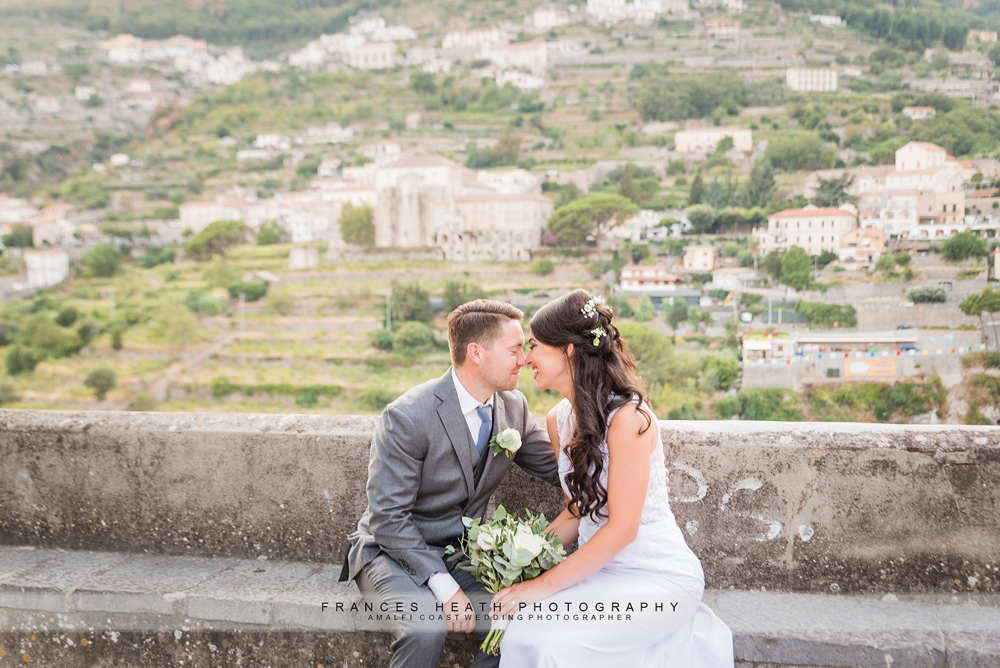 Bride and groom sitting on bench in Ravello