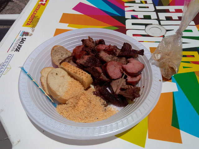 The barbecue plate with meat, sausages and bread slices.