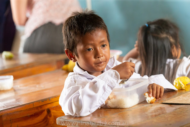 Cambodian boy, around 5 years of age, is eating his lunch of rice and an egg from his plastic container whilst sitting at his school desk