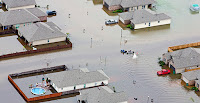 A boat motors among flooded homes in Hammond, La., after heavy rains inundated the region around Baton Rouge on Saturday. (Photo Credit: AP Images) Click to Enlarge.