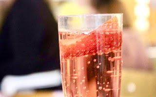 A zoomed in glass of bubbly Prosecco on a bright background.