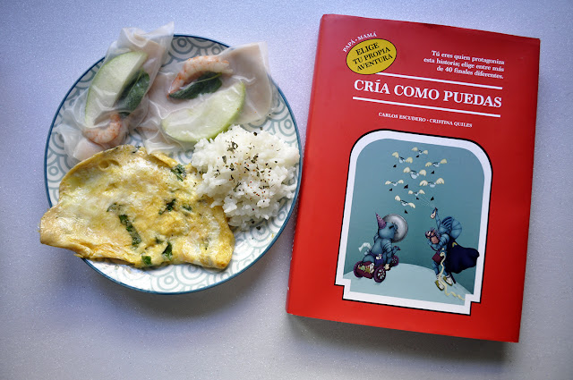 Tortilla, rollitos trasparentes donde se ven manzana hierbabuena y gambas, y arroz. El libro es rojo, se ven a una madre y un padre peleando contra pañales y se lee elige tu propia aventura