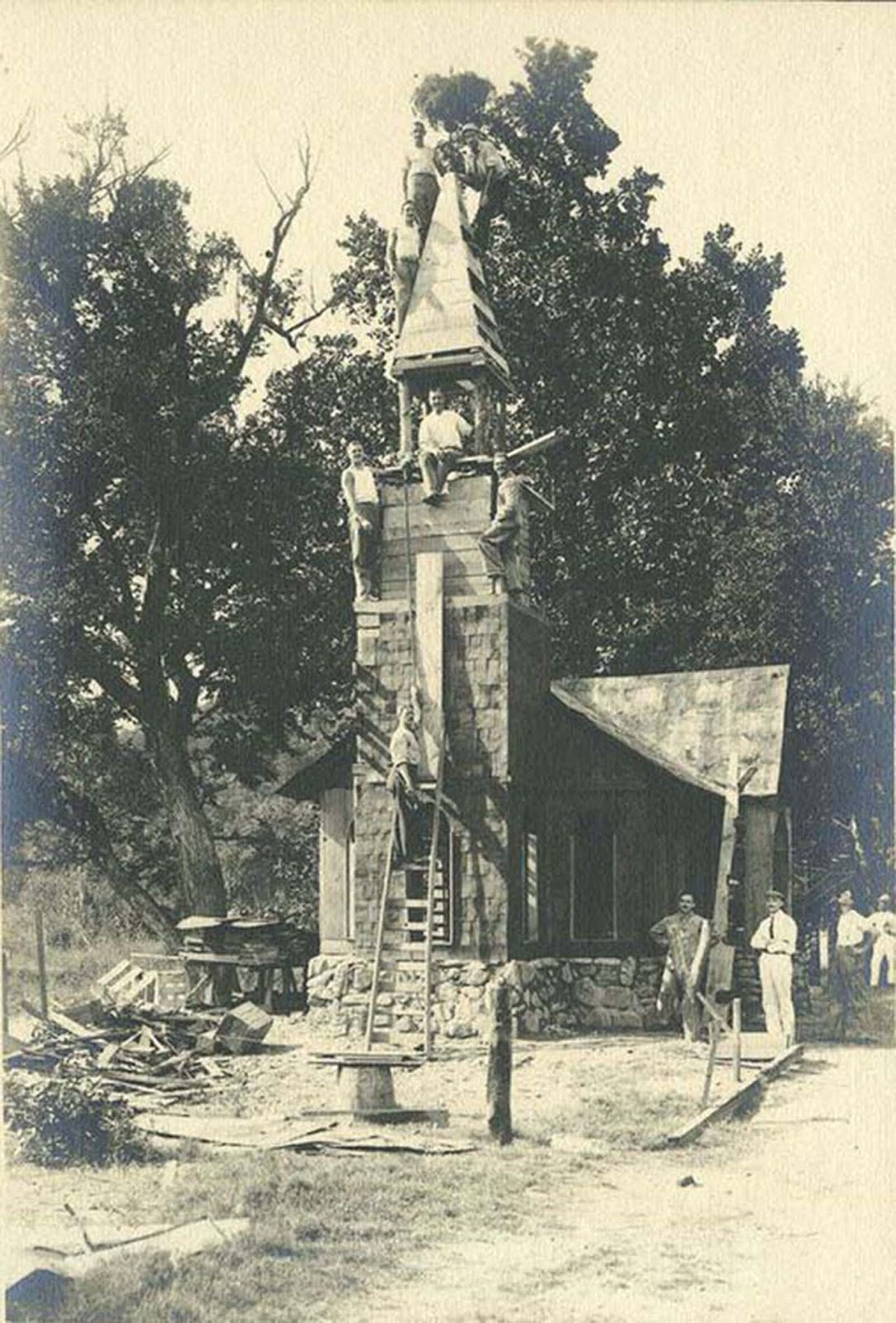 Internees work on the construction of a church in the camp village.