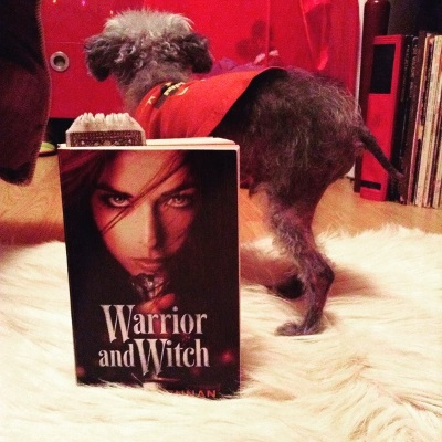 Murchie stands on a white fur rug, his back to the viewer. He wears his orange t-shirt. In the foreground is a paperback copy of Warrior and Witch, featuring a red-haired white woman clutching a sword beneath her chin as she stared out at the viewer.