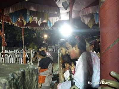 Devotees look on as Ganesh Visarjan takes place in a local Ganesha Temple