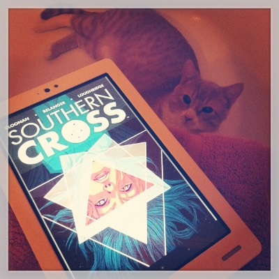 Ollie reclines in a bathtub. On the ledge above him is a white Kobo with Southern Cross's cover on its screen. The cover features a pale-skinned person's face suspended upside down within a triangle surrounded by a white, seven-point star in a sea of deep blues.