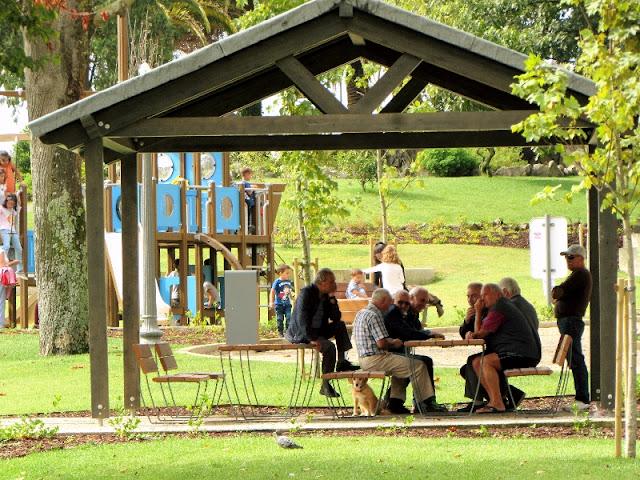 Senhores jogando cartas em mesa do Jardim do Morro