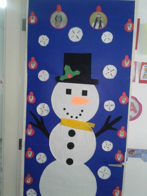 Decoração de porta com Boneco de Neve e  bolinhas natalinas com fotos dos professores e alunos.