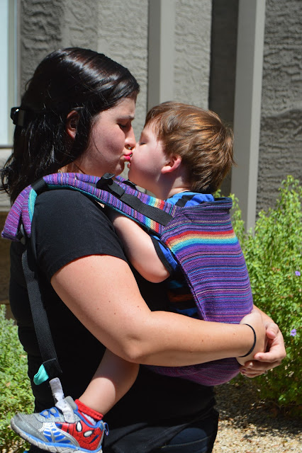 Image of fair skin woman with dark hair kissing fair skin brown haired toddler worn in a front carry in a purple onbu with rainbow stripes