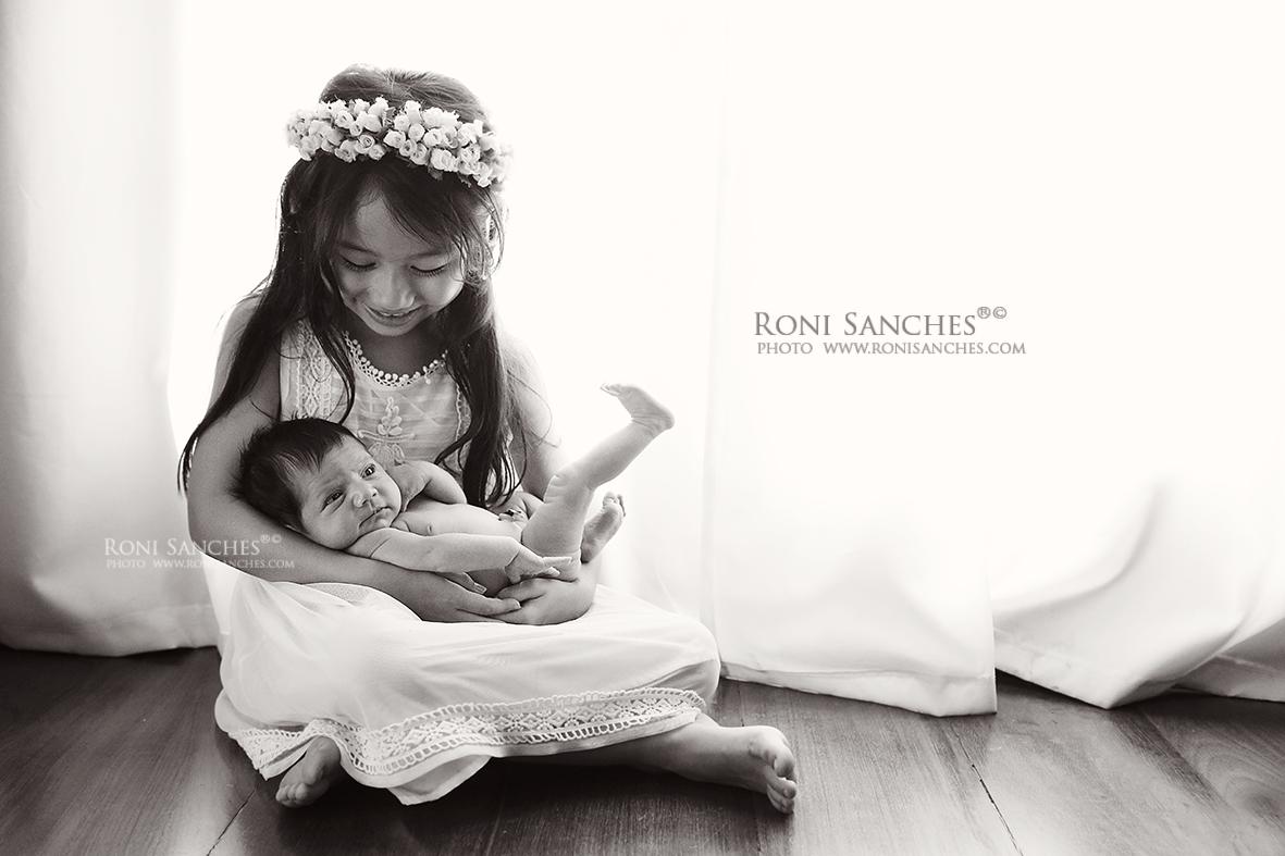 os irmãos participam da sessão de fotos newborn com o bebê