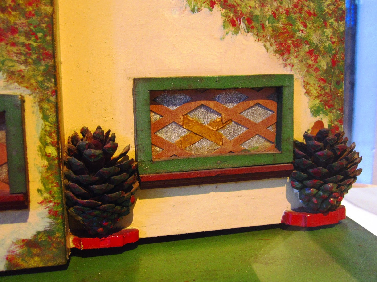 Close up of a vintage doll's house window, with trees in front of it, made of pine cones.
