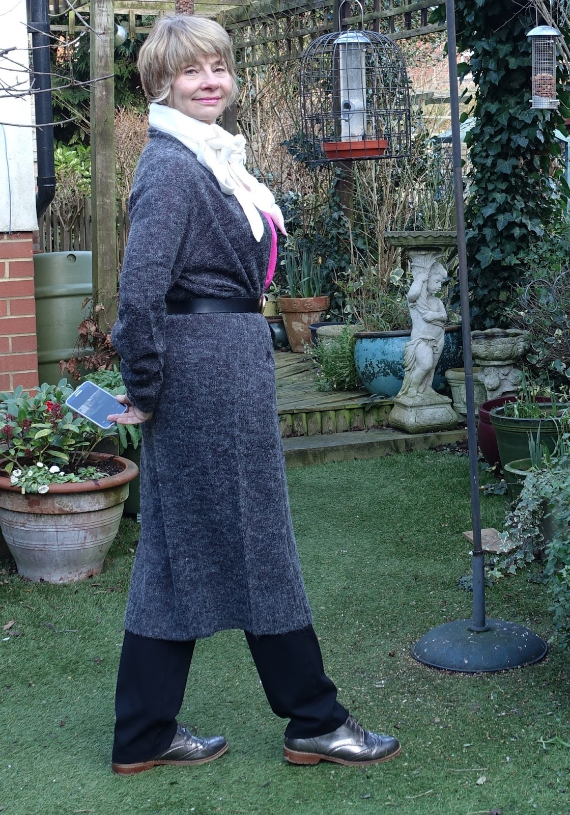 Image showing a middle aged fashionista wearing a belted long line cardigan in  grey worn over black trousers and metallic brogues. A cream fleecy scarf adds interest.