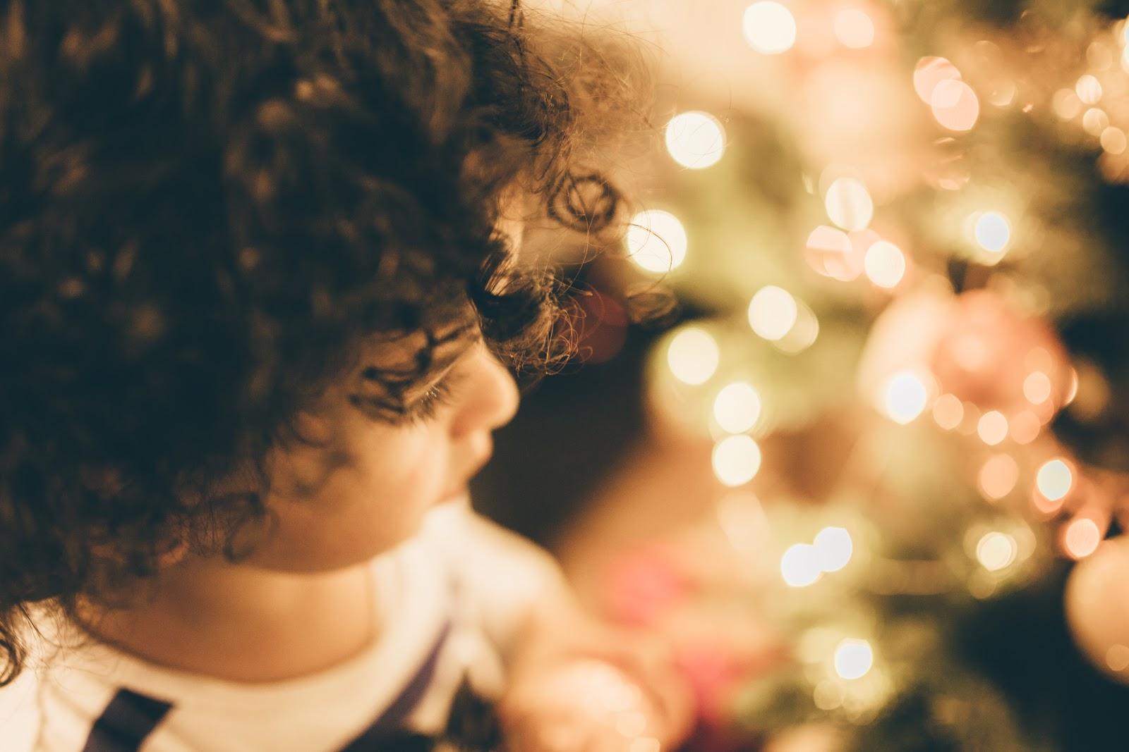 クリスマスの明るい飾り付けの部屋に立つ子供