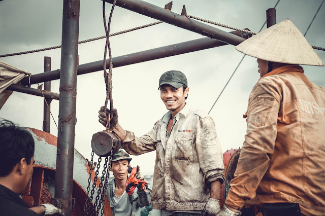Crew of fishermen, workers working, man smiling