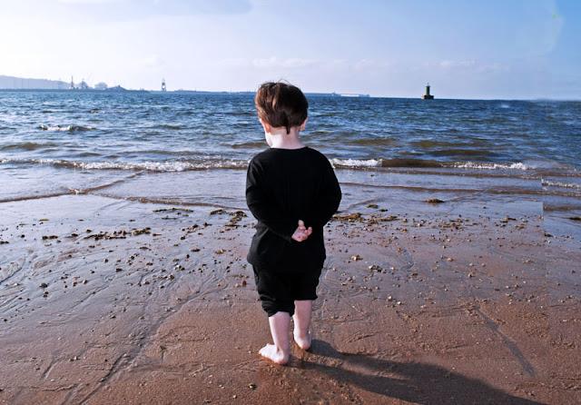 pixelillo vestido de negro con las manos enlazadas a la espalda, los pantalones remangados hasta la rodilla, mirando las olas acercarse a la orilla