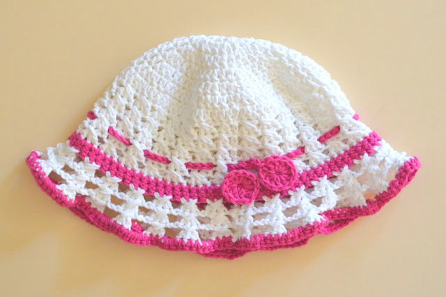 A toddler hat in white and hot pink.  It has a solid crown with an open crossed stitch pattern on the sides and brim.  It has a thin band of hot pink either side of the brim.  It also has a hot pink drawstring which is finished with circle motifs to prevent the drawstring from slipping out of the hat.