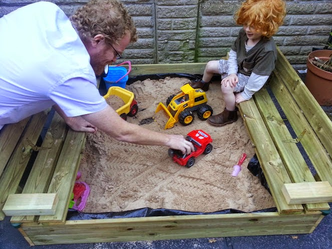 4 year old sitting playing in sand pit with cars and vehicles