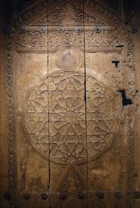 Üzerinde yıldız ve çeşitli süsleme motifleri bulunan el oyması eski bir kapı