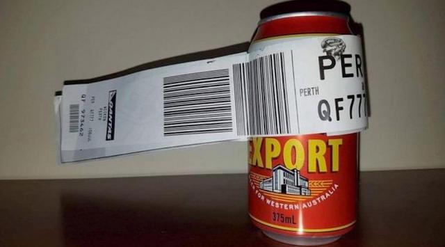 Sebuah kaleng bir dengan stiker bagasi tampak keluar dari bagage conveyor