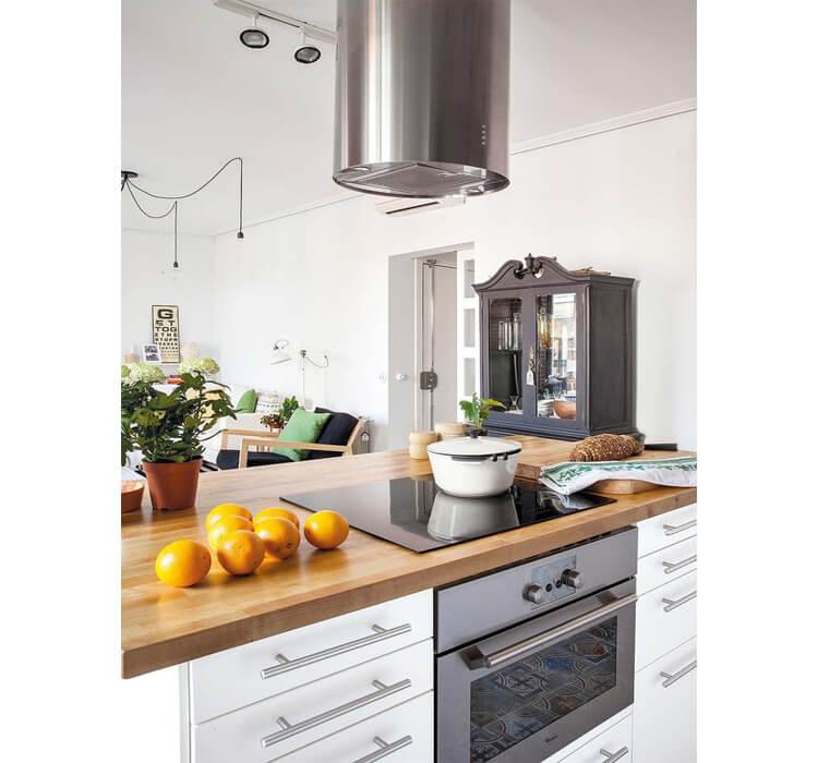 Cappa, forno e top in legno di una cucina bianca