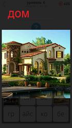 Около водоема на возвышении стоит великолепный дом
