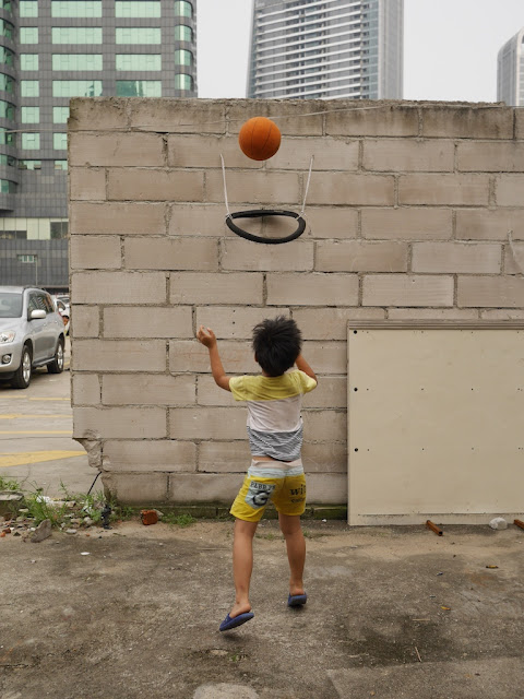 boy shooting a basketball into a bicycle tire hoop in Zhuhai, China