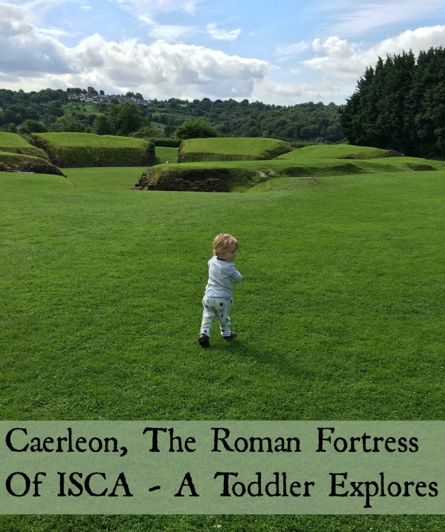 Caerleon-the-roman-fortress-of-isca-a-toddler-explores-text-on-picture-of-toddler-with-ruins-behind