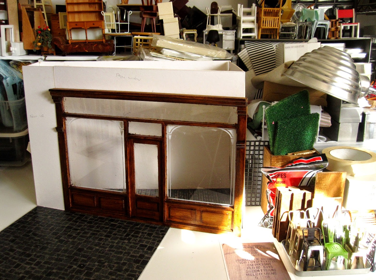 Modern dolls' house miniature half-built cafe on a work table.