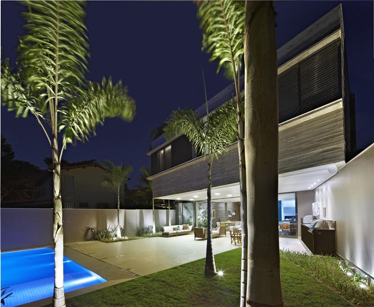 Backyard of modern home by Anastasia Architects at night