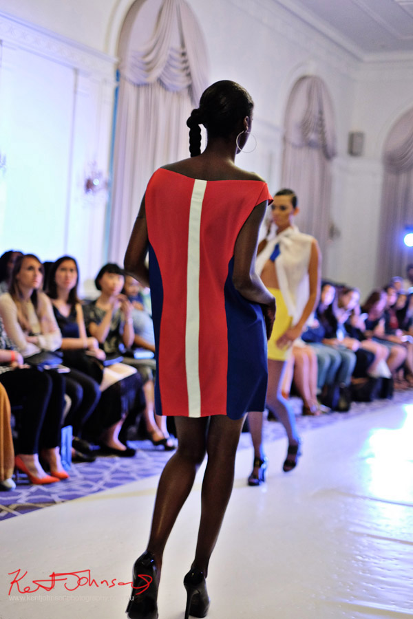 Back view of a model wearing a bold red with navy blue dress with a white vertical stripe. André Bryson - Guerrilla - NYFW. Photographed for Street Fashion Sydney by Kent Johnson.
