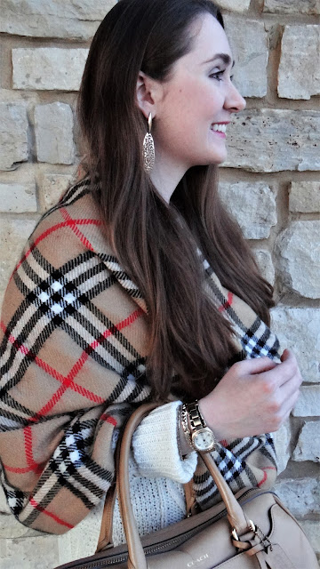 Model is wearing oversize white knit sweater with a Burberry plaid shawl and gold accessories.