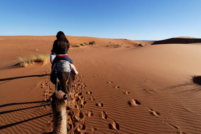 Lena sobre un camello en el desierto de Erg Chebbi
