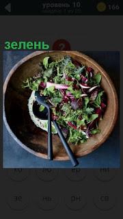 положена зелень в тарелку и вилка с ложкой